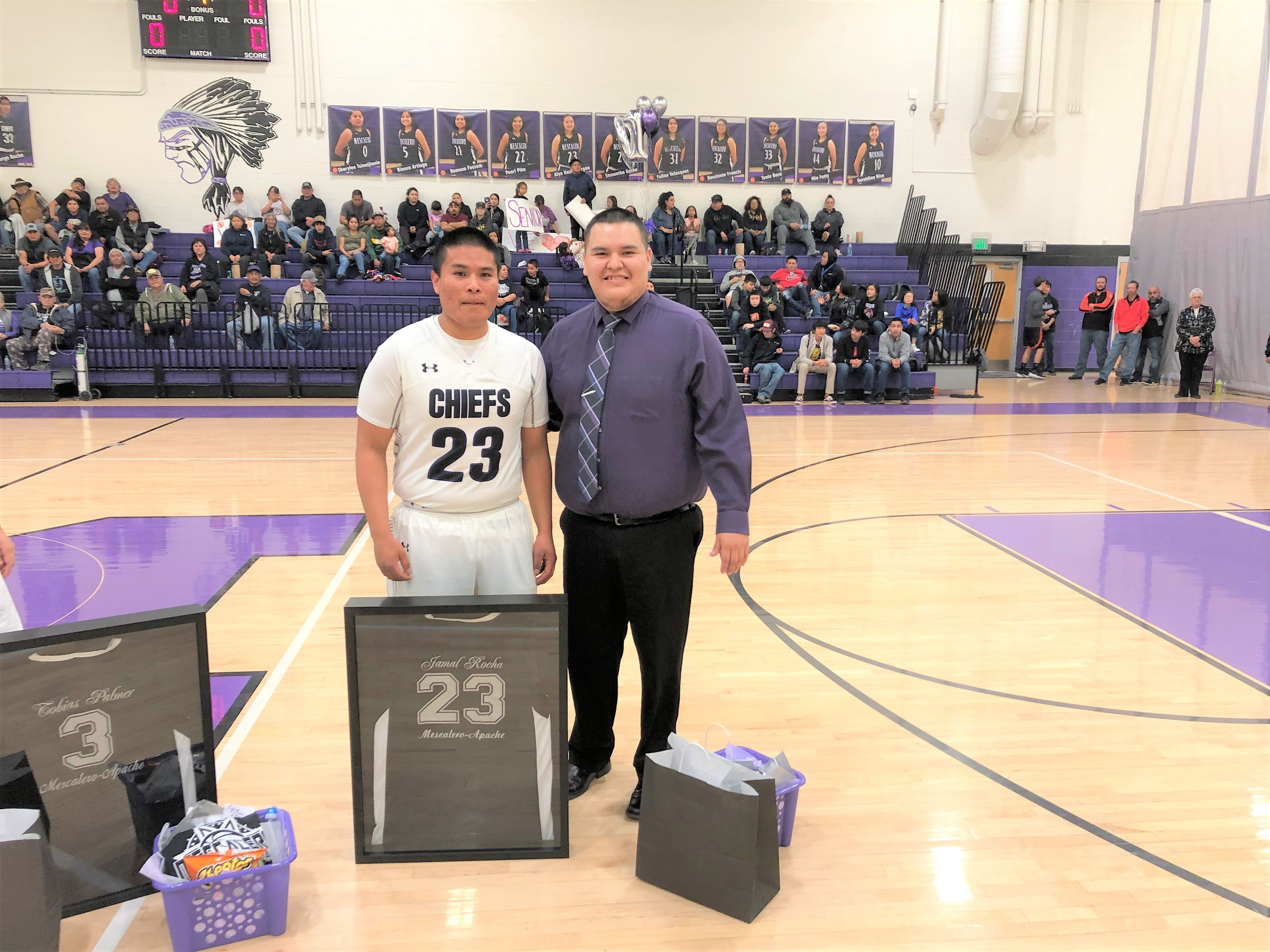 Jamal Rocha, #23 and Coach Kane of the Mescalero Apache Varsity Basketball team, show off their school spirit and pride next to a newly framed jersey.