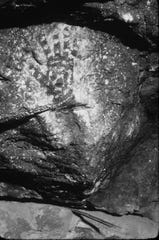 A decorated hand print is one of the archaeological treasures in the Feather Cave.