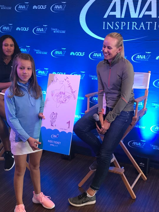 Lillian Clark, 9, of Indio shows off her artwork which was chosen for children's ticket for the ANA Inspiration next month. Defending ANA champion Pernilla Lindberg signed the original art for Clark at the ANA Inspiration Media Day Monday.