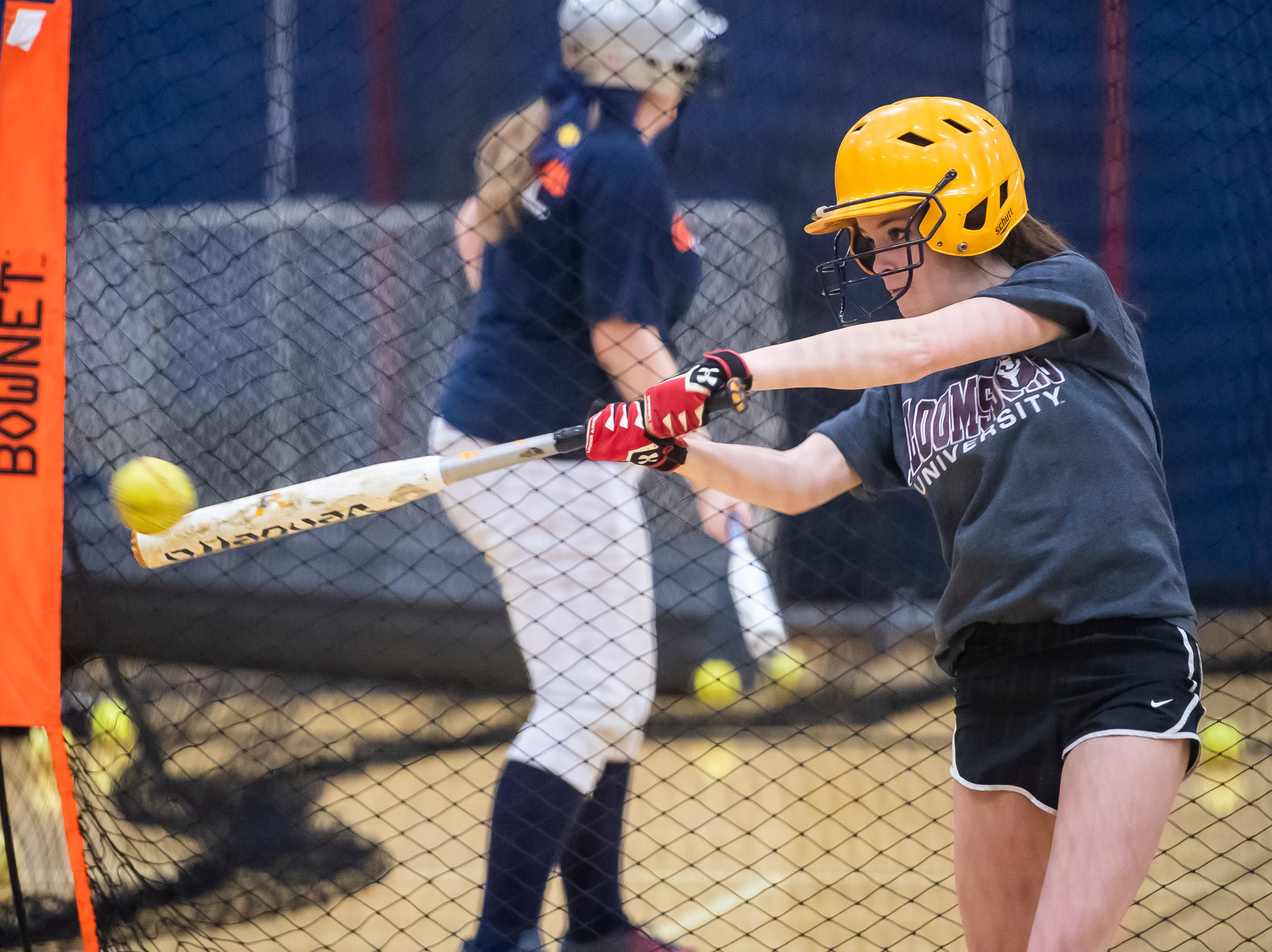 Littlestown's Jada Mummert connects with a pitch inside the batting cage on the first day of softball practice in the Littlestown High School gym Monday, March 4, 2019.