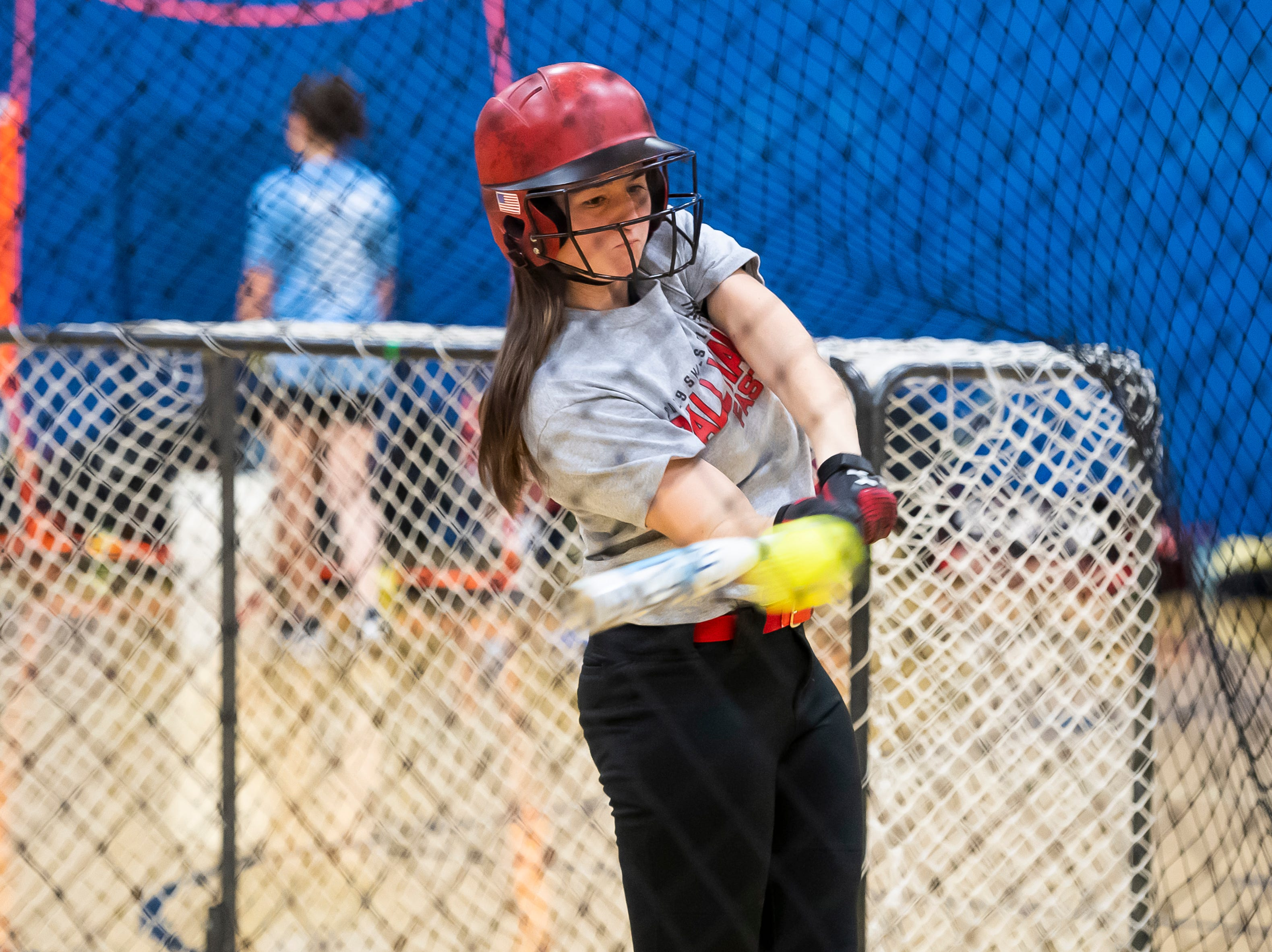 Littlestown's Amaya Bowman connects with a pitch inside the batting cage on the first day of softball practice in the Littlestown High School gym Monday, March 4, 2019.