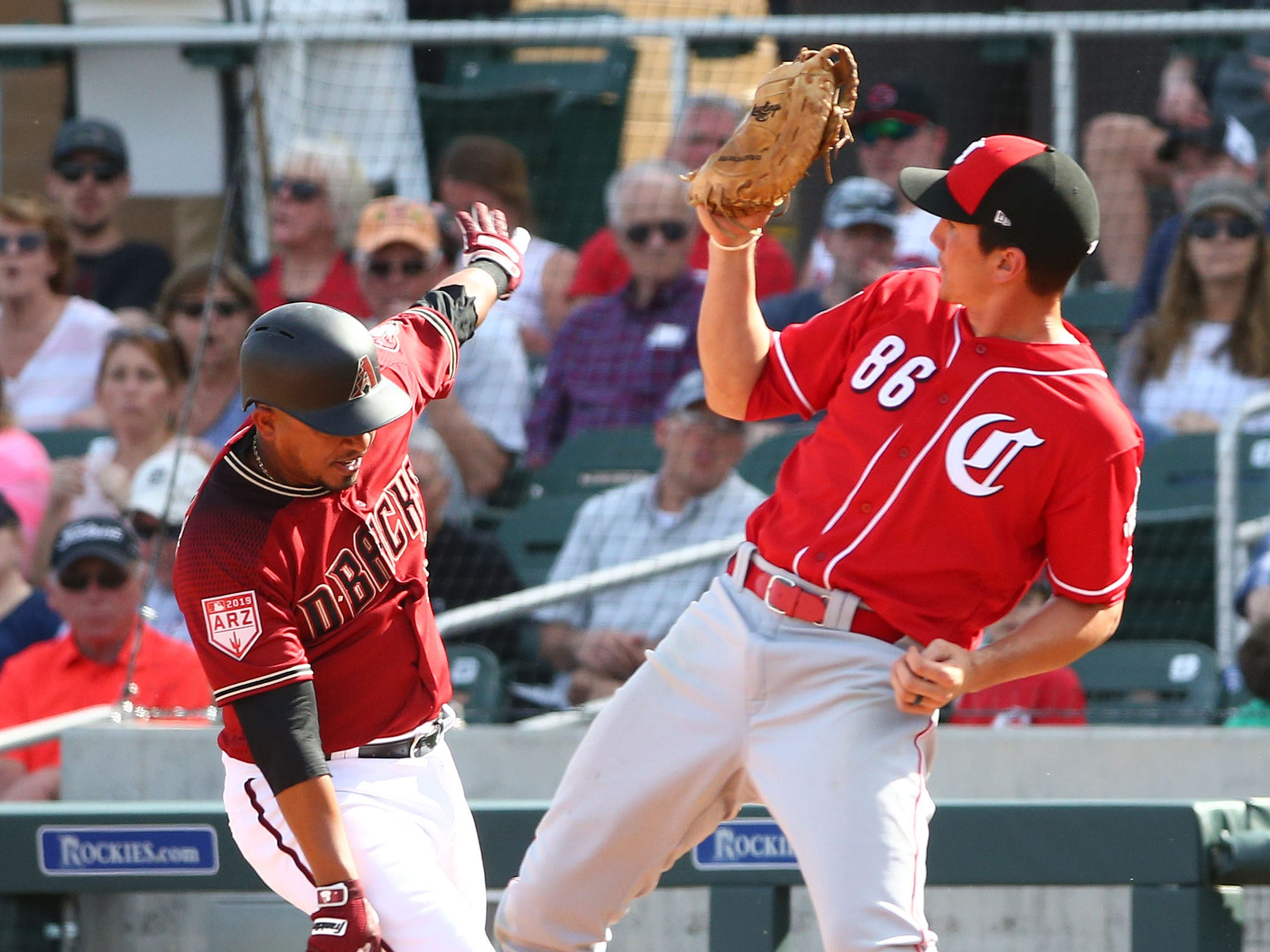 Arizona Diamondbacks Eduardo Escobar trips over Cincinnati Reds first baseman Jordan Patterson (86) in the 5th inning during a spring training game on Mar. 4, 2019, at Salt River Fields in Scottsdale, Ariz.
