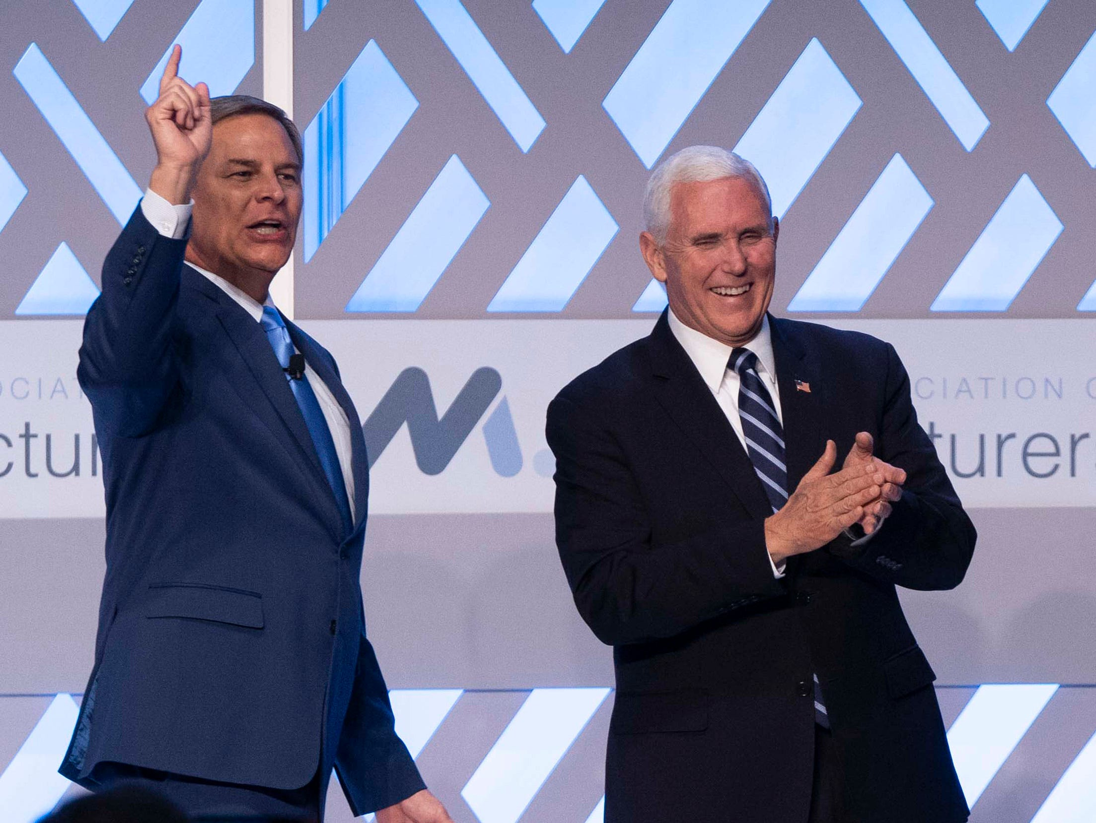 Jay Timmons (left), president and chief executive officer of the National Association of Manufacturers, and Vice President Mike Pence speak to representatives of the National Association of Manufacturers at the Phoenician resort in Phoenix on March 5, 2019.