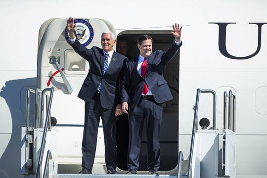 Vice President Mike Pence and Arizona Gov. Doug Ducey wave after walking off Air Force Two at Sky Harbor International Airport in Phoenix on March 5, 2019.