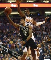 Milwaukee Bucks guard Eric Bledsoe (6) puts a shot up against Phoenix Suns center Deandre Ayton (22) during the second quarter in Phoenix March 4, 2019.