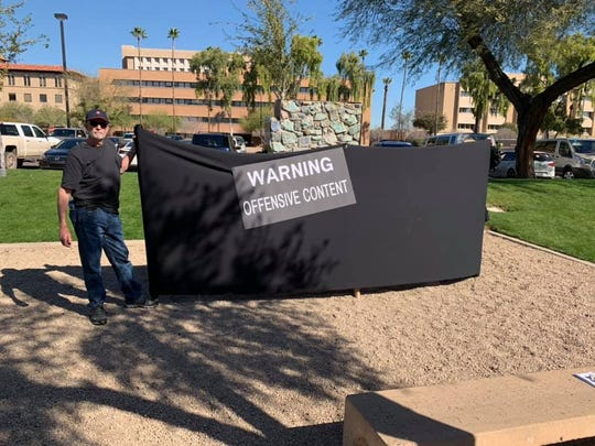 """Protesters urging removal of Arizona's Confederate memorials draped a black """"warning"""" curtain over the monument at the state Capitol on Tuesday, March 5, 2019."""