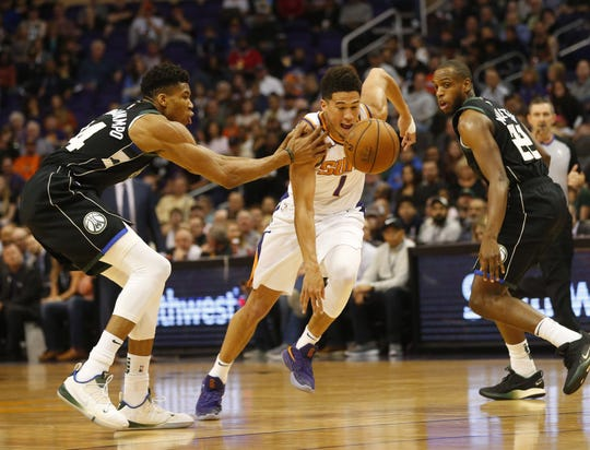 Phoenix Suns guard Devin Booker (1) is fouled by Milwaukee Bucks forward Giannis Antetokounmpo (34) during the first quarter in Phoenix March 4, 2019.