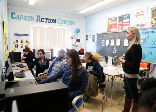 Career Action Center director Katrina Gobins talks with students as they work on their FAFSAs at Poughkeepsie High School on March 1, 2019.