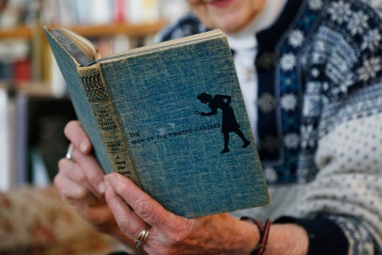 """Mary Heller looks over her 1933 copy of Nancy Drew and """"The Sign of the Twisted Candles"""" at her home in the Town of Poughkeepsie on March 1, 2019."""