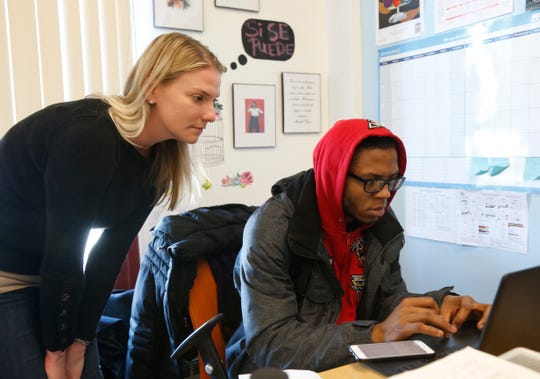 Career Action Center director Katrina Gobins talks with Jahquel Harvard as he works on his FAFSA at Poughkeepsie High School on March 1, 2019.
