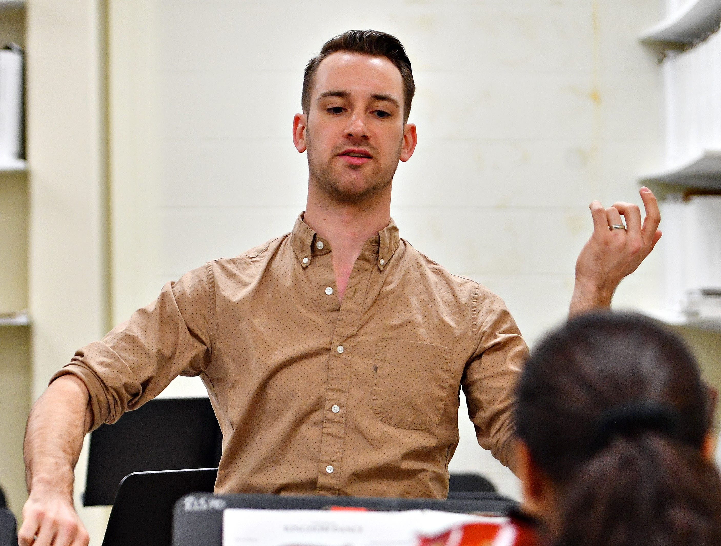 """Red Lion alumnus Derek Cooper, who is a working composer in New York, gestures while working with a student ensemble as they practice """"Kingdom Dance,"""" from the Disney film, """"Tangled,"""" at Red Lion Area High School in Red Lion, Tuesday, March 5, 2019. Dawn J. Sagert photo"""