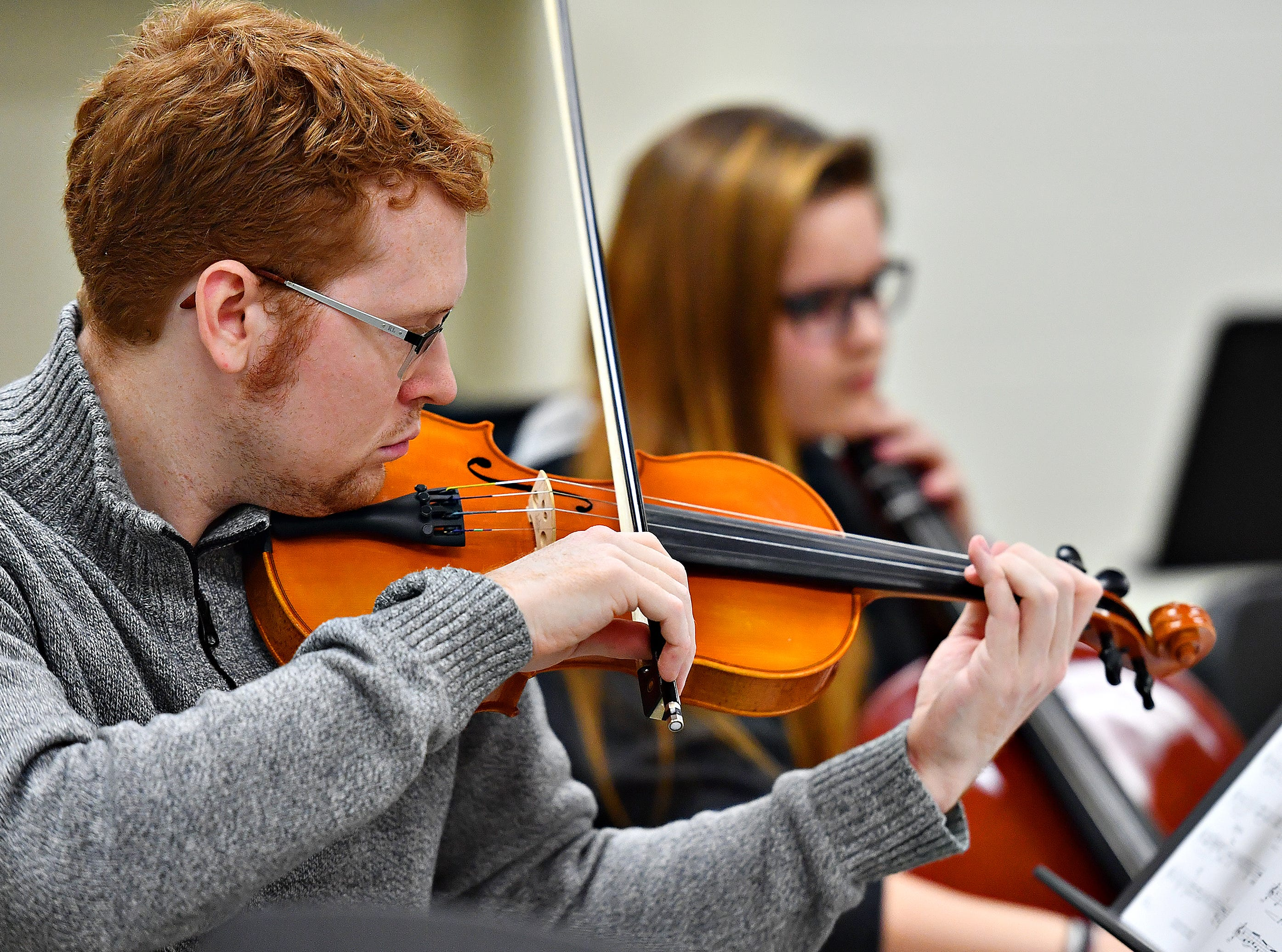 """Orchestra Director Scott Kaliszak, front, plays violin while student Kate Deery plays cello as a student ensemble works with Red Lion alumnus Derek Cooper, who is a working composer in New York, as they practice for their upcoming performance at Red Lion Area High School in Red Lion, Tuesday, March 5, 2019. The orchestra will debut Cooper's composition of """"Obsidian Rainbow"""" during their performance on March 6. Dawn J. Sagert photo"""