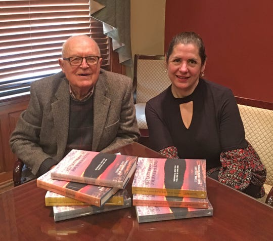 """Attorney J. Ross McGinnis and York County Bar Association/Bar Foundation CEO Victoria Connor with sets of the Memorial Minutes entitled """"Reflections at Journey's End."""""""