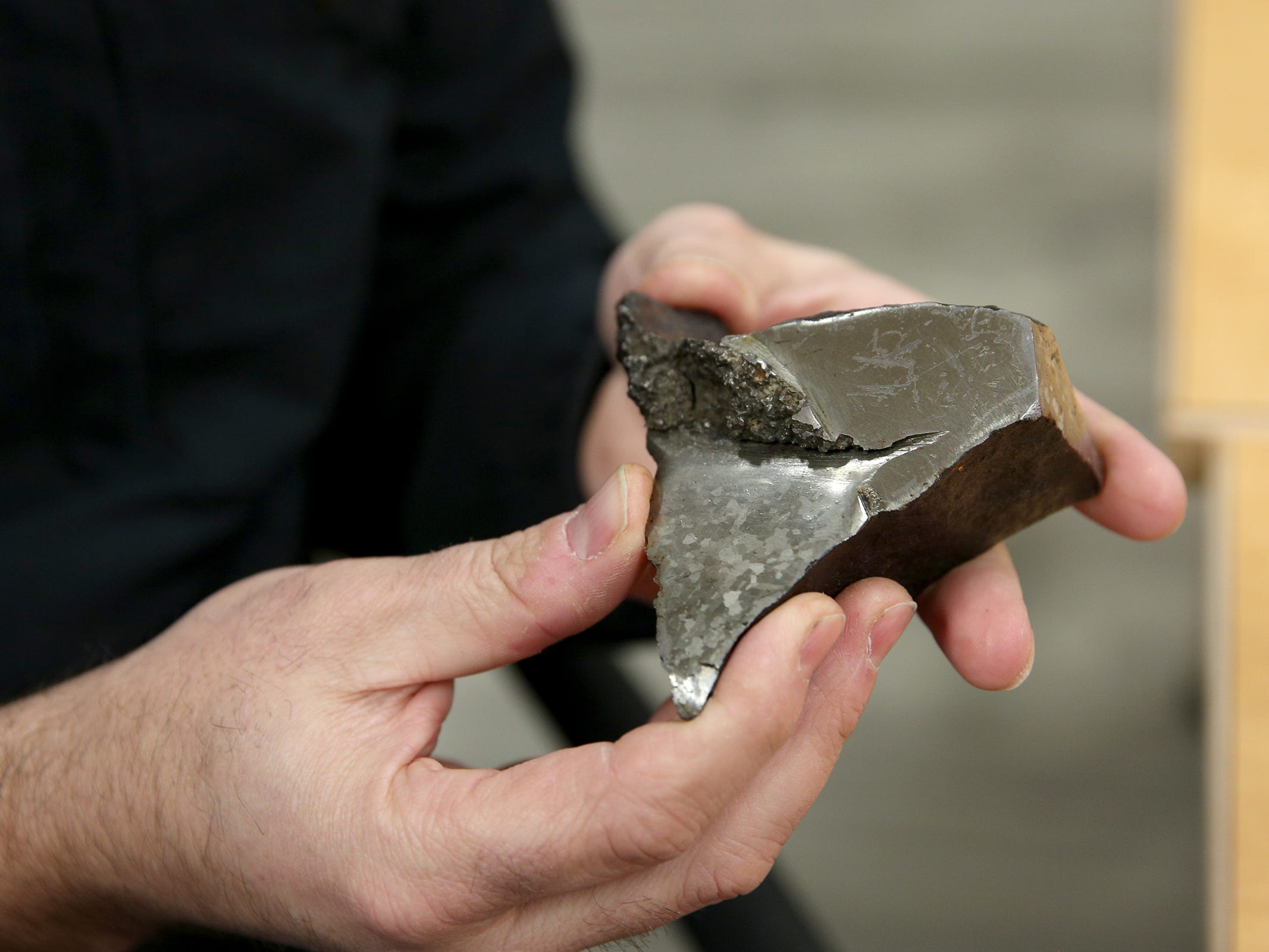 The Confederate Tribes of Grand Ronde Interpretive Coordinator, Travis Stewart, holds a piece of the meteorite Tomanowos, at the Chachalu Museum and Cultural Center in Grand Ronde on Thursday, Feb. 28, 2019.
