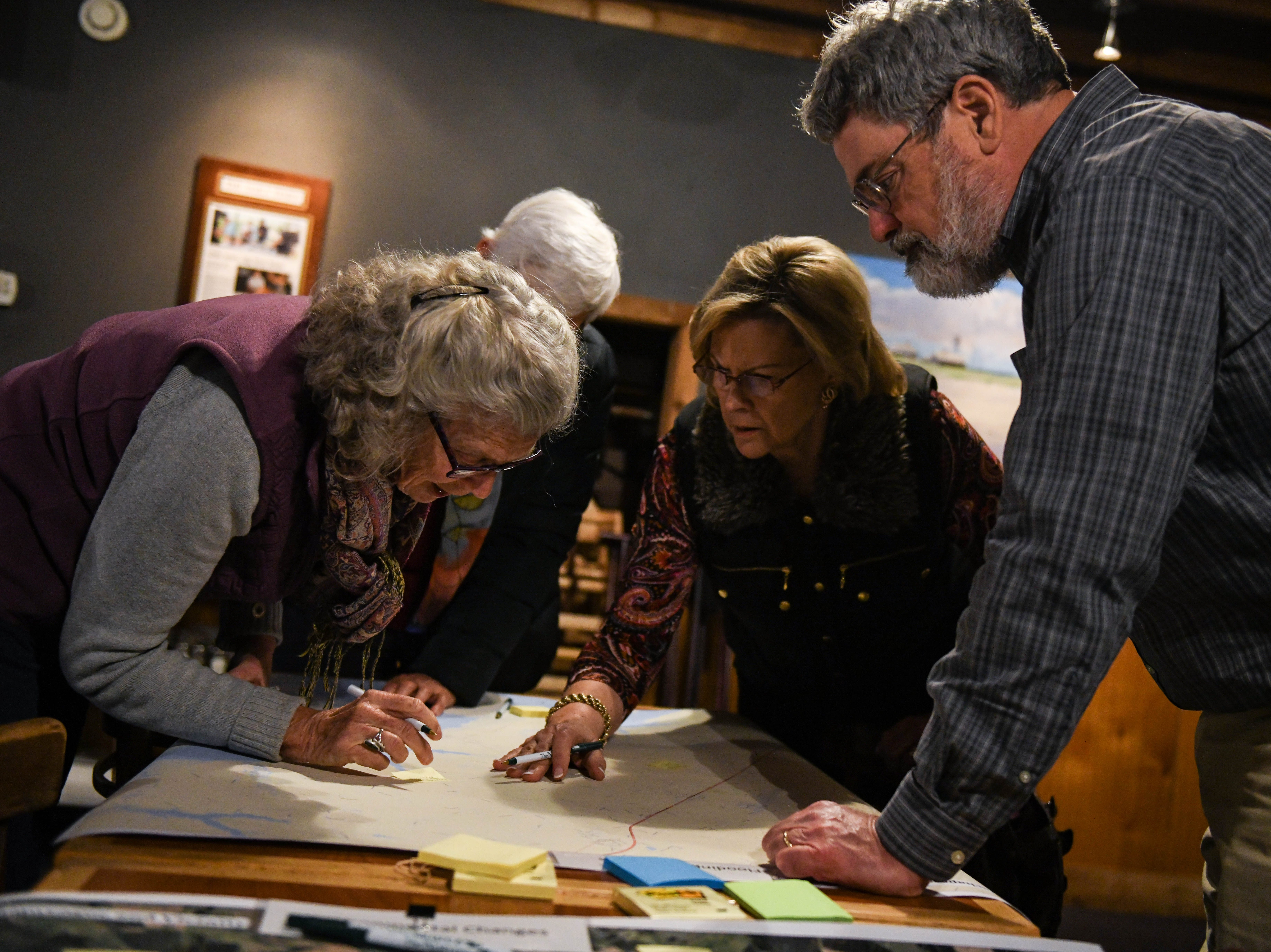Local residents, Lloyd Johnston (left) and Dianne Nickel work with the Nature Conservancy's Jim McGowan to map local flooding at a community meeting in Wachapreague, Virginia on Monday, March 4, 2019.