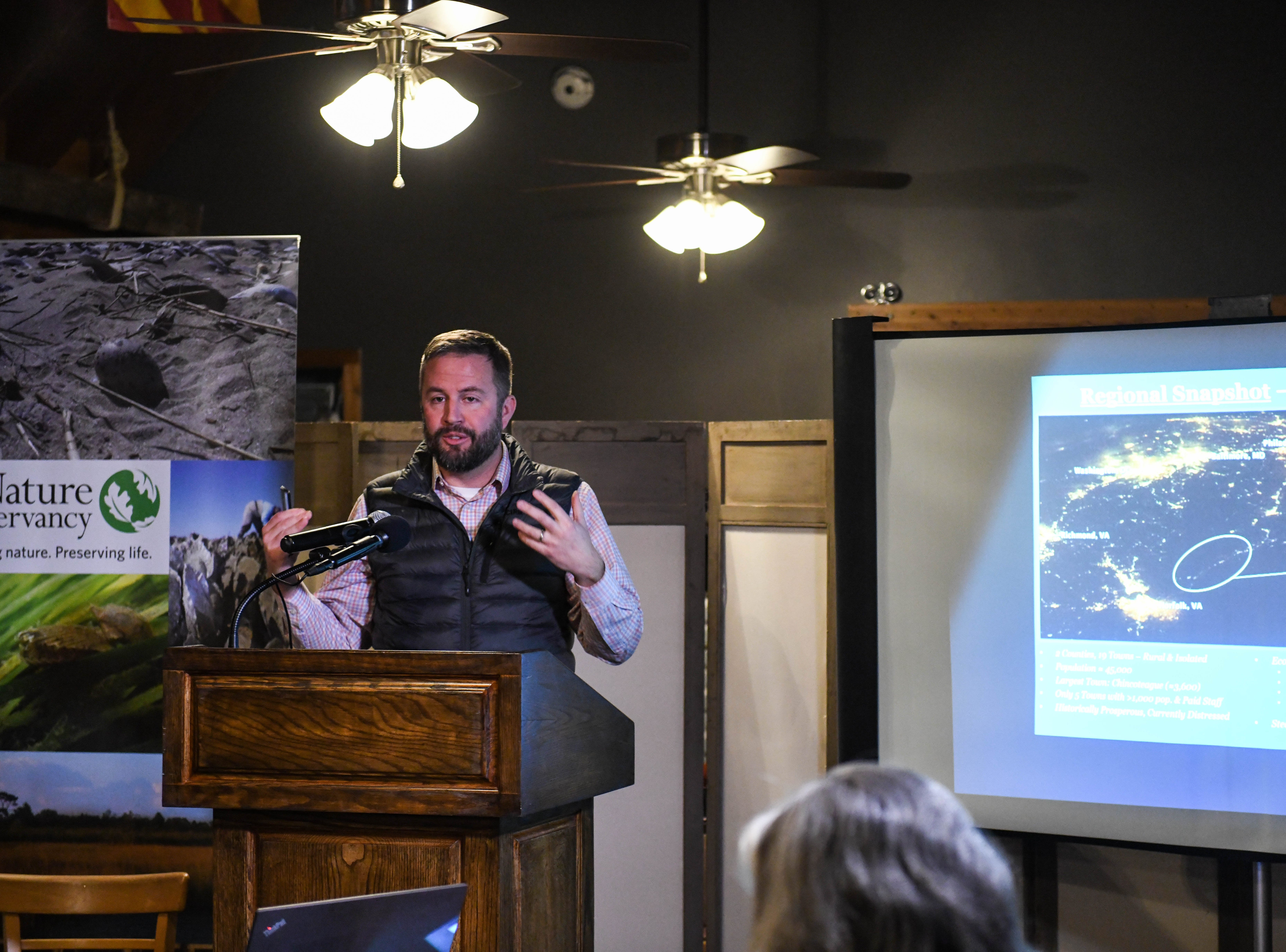 Curtis Smith, director of planning for the Accomack- Northampton Planning District Commission, presents about sea level rise at a community meeting in Wachapreague, Virginia on Monday, March 4, 2019.