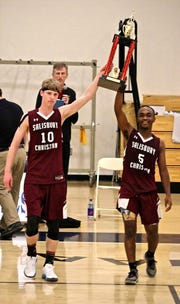 Salisbury Christian seniors Caleb Mitchell (right) and Mark Nyce hold up the championship trophy on Saturday, March 2, 2019.