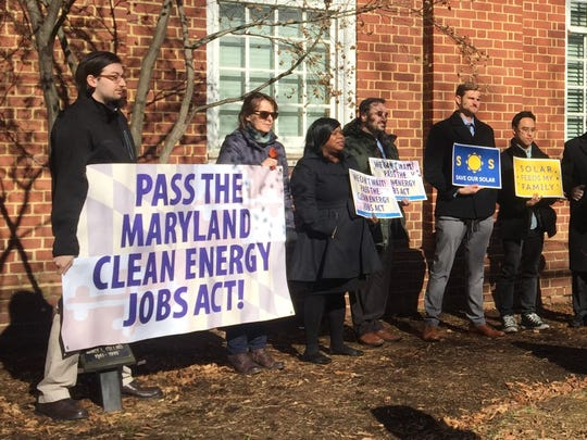 Advocates hold signs in support of the Maryland Clean Energy Jobs Act at a press conference in Annapolis on Tuesday, March 5, 2019.