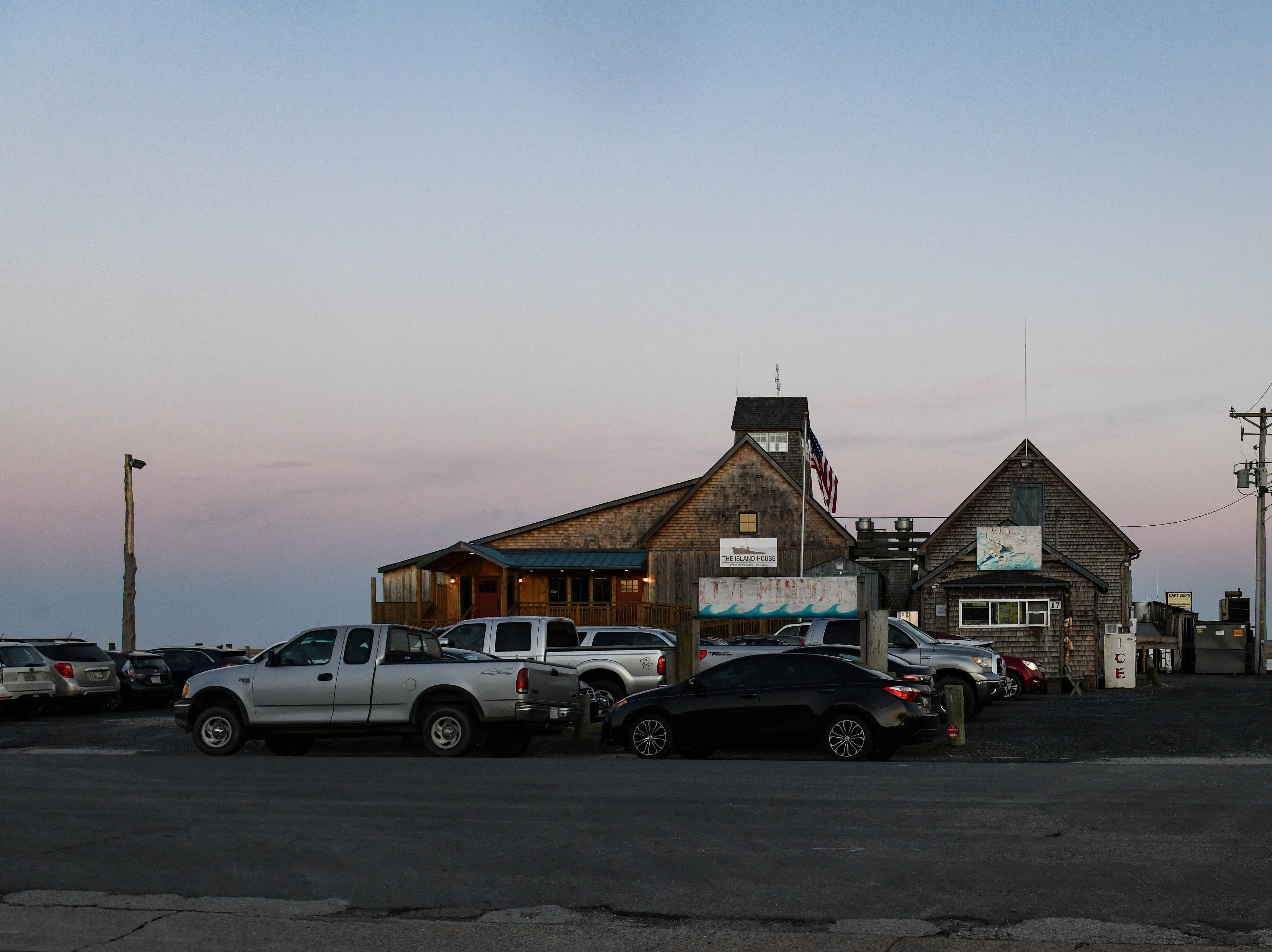 Cars crowd outside the Island House Restaurant in Wachapreague, Virginia for a community discussion on flooding and  sea level rise led by the Nature Conservancy on Monday, March 4, 2019.