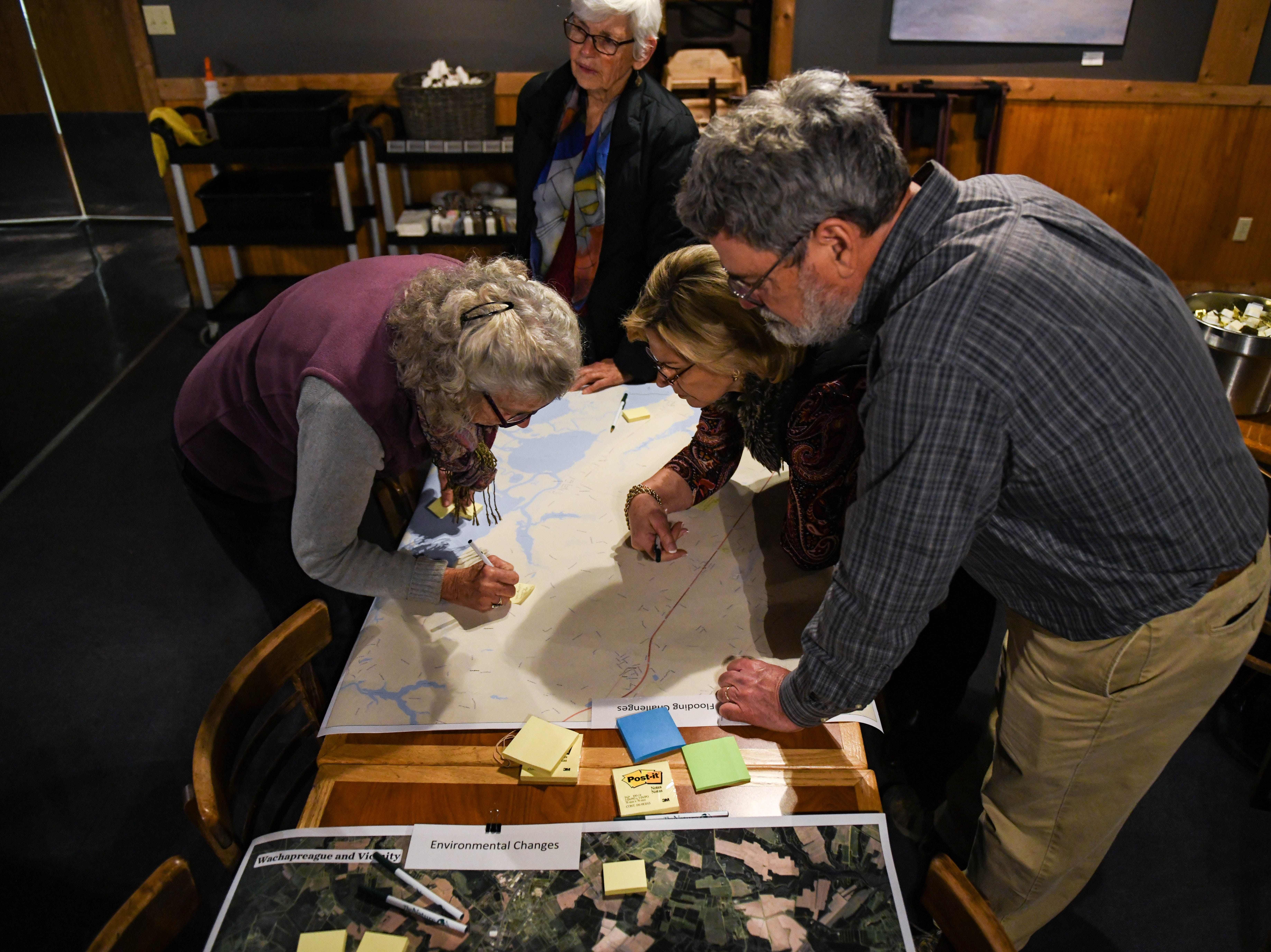 Local residents, Lloyd Johnston (left) and Dianne Nickel work with the Nature Conservancy's Jim McGowan to map local flooding at a community meeting in Wachapreague, Virginia on Monday, March 4, 2019. Locals were asked to put informational post-it notes on roads where they had seen flooding.