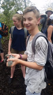 Harrisburg South Middle School eighth-grader helps tag and release an iguana in Utila, Honduras in summer 2018 as part of an environmental service project to stop plastic pollution.