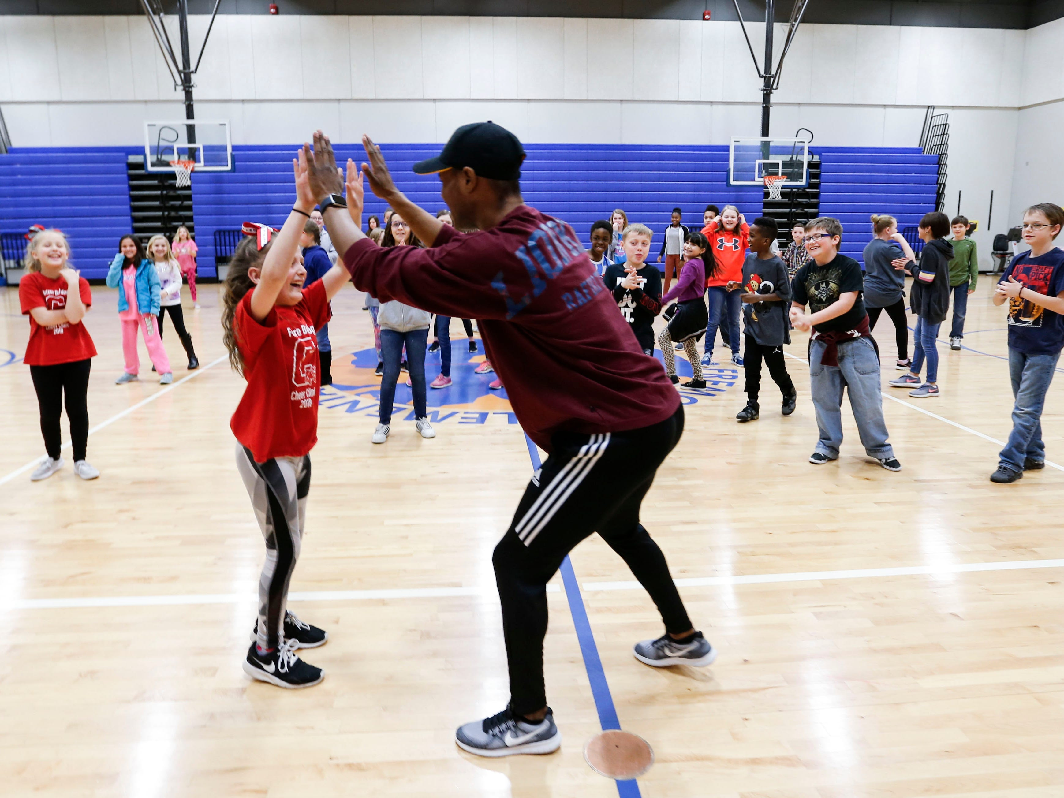 """""""Lion King"""" cast member Courtney Thomas high-fives Fremont Elementary  School student Victory Stine after she successfully performed the dance moves taught to the students as part of Disney's Get Up and Go Workshop on Tuesday, March 5, 2019."""