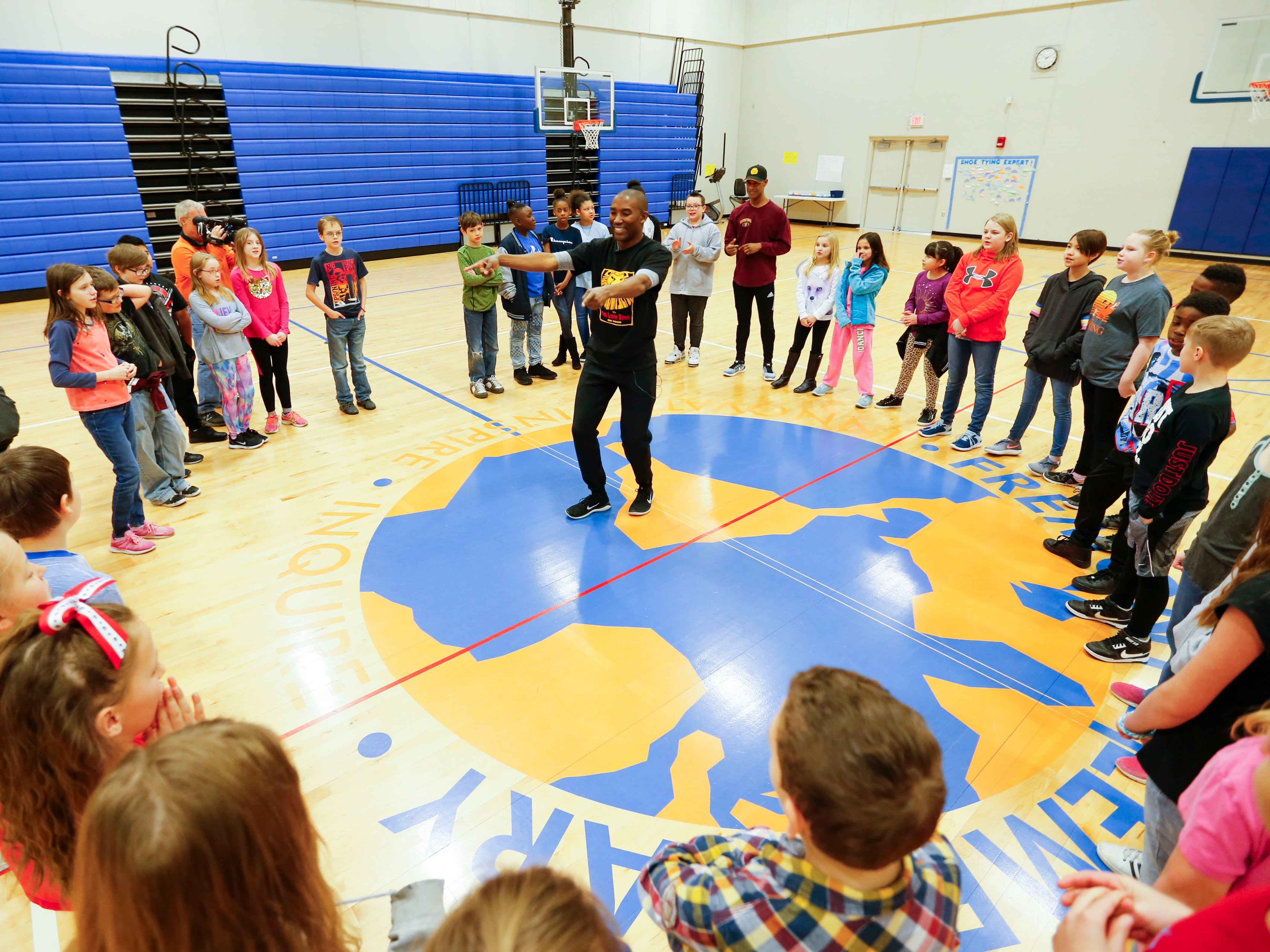 """""""Lion King"""" cast member Andrew Arrington dances in the middle of a circle of Fremont Elementary students as part of Disney's Get Up and Go Workshop on Tuesday, March 5, 2019."""