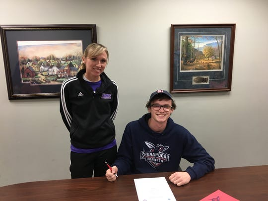 Waynesboro senior runner Patrick Maneval, sitting beside his coach Julie Stevens, announced Tuesday he'd be attending Shenandoah University, where he'll run cross country and track.