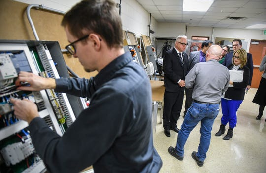 Gov. Tim Walz and Lt. Gov. Peggy Flanagan visit the automation lab as Cody Sovereign works on a project Tuesday, March 5, during a tour of St. Cloud Technical and Community College.