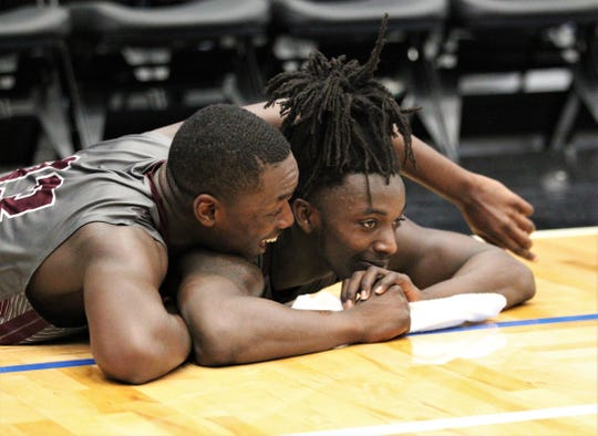 Madison County's Demarvion Brown jumps on senior Travis Jay as he soaks in the Cowboys capturing a Class 1A state championship with a 62-60 overtime victory against Wildwood at the RP Funding Center in Lakeland on Tuesday.