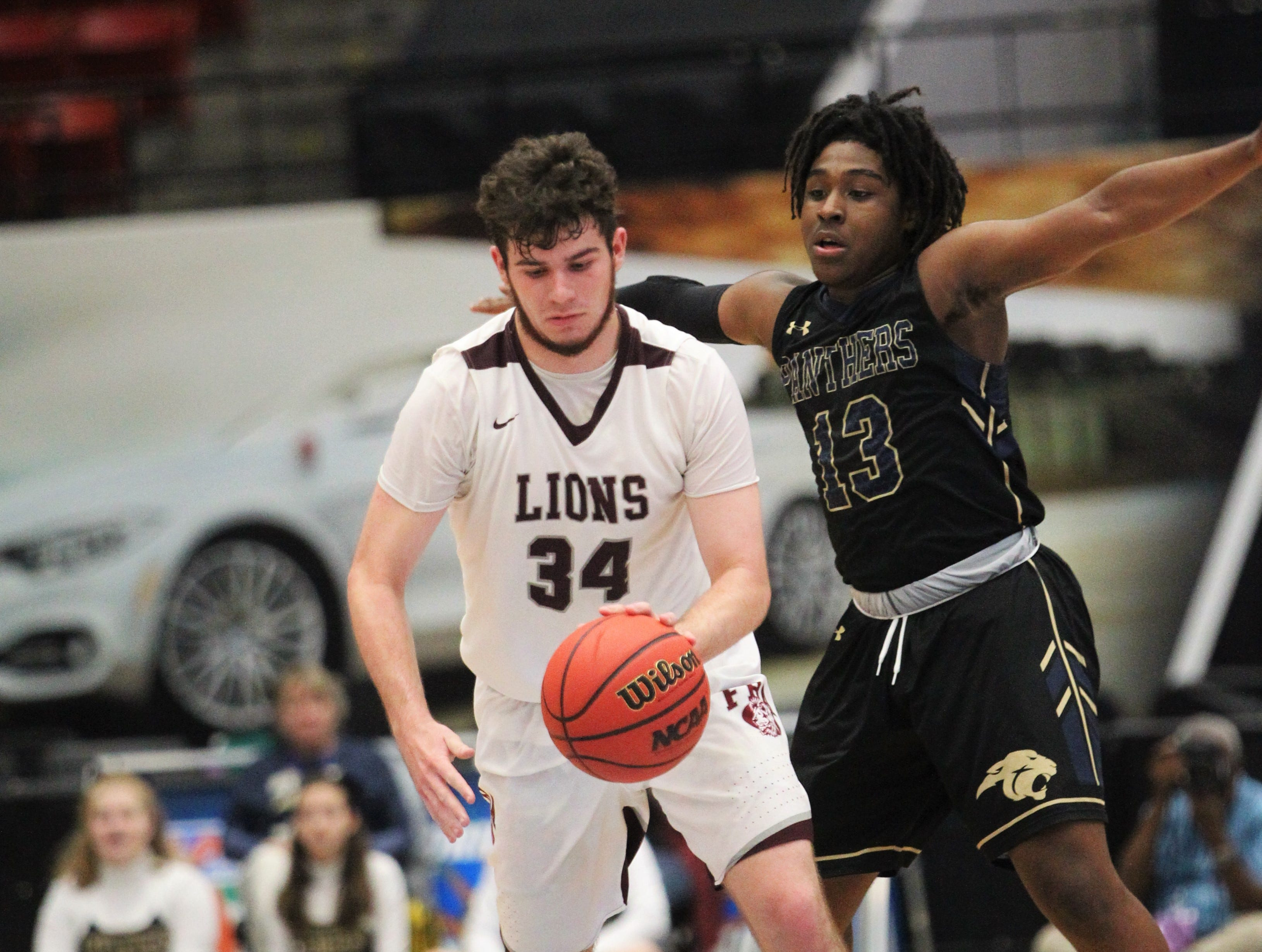 First Baptist Academy's Trevor Tracy tries to hold off St. John Paul II's Tyreke McElwain as the Panthers beat FBA 55-37 during a Class 3A state championship game at the RP Funding Center in Lakeland on March 4, 2019.