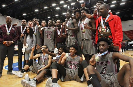 Madison County's basketball team celebrates a Class 1A state championship with a 62-60 overtime victory against Wildwood at the RP Funding Center in Lakeland on Tuesday.