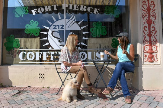 "Kathleen Grace (right), owner of the new  Fort Pierce 212° Coffee House, takes a break to talk with Kimberly Bobjak, and her dog Lola, of Port St. Lucie, on Monday, March 4, 2019, while working at her new coffee shop at 127 North Second Street, across from Sailfish Brewing Co. in Downtown Fort Pierce. ""I like coffee,"" Grace said. ""It's a 25-year-old dream of mine to open a coffee house, to have people come together and congregate and just escape the busyness of their day and come and have a feel-good experience with favorite drinks or treats or an atmosphere. I like serving people."""