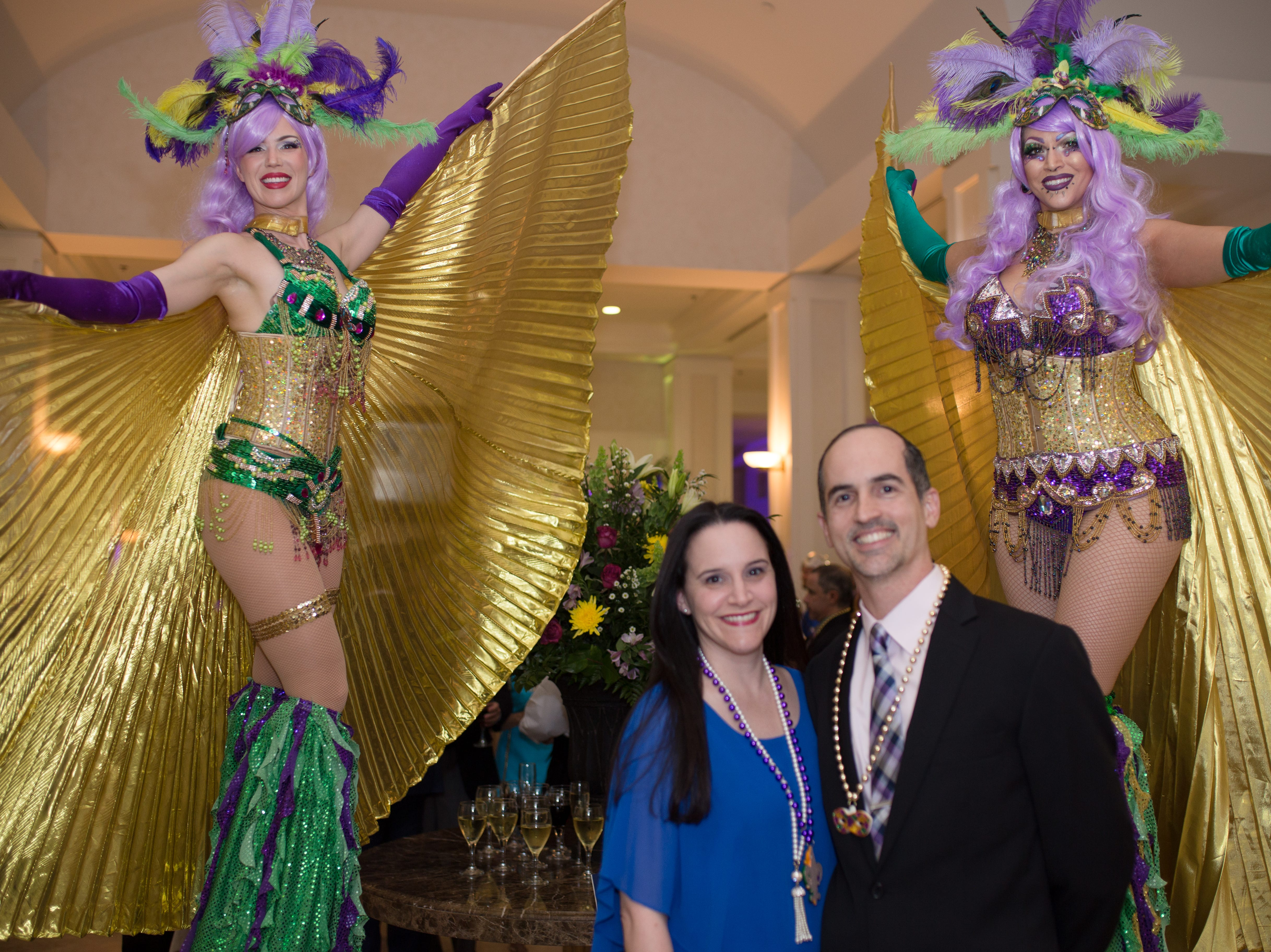 Stiltwalkers surround Sonia Peter and Dr. Arley Peter, a We Care physician, as they enjoy Mardi Gras at the Oak Harbor Club on March 1.