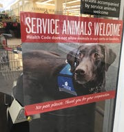 This sign in the window of the Jensen Beach Winn-Dixie welcomes service animals - but not pets.