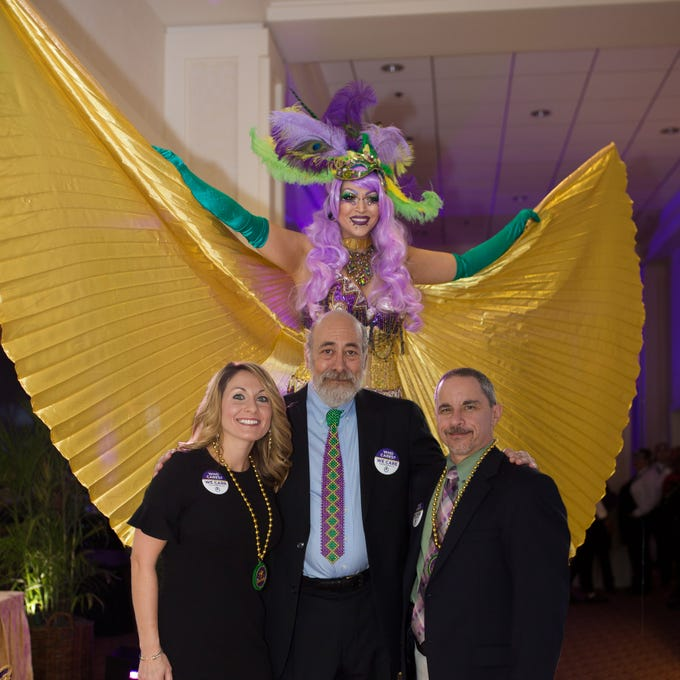 The We Care Program celebrated its 28th year March 1 during its Mardi Gras Celebration at Oak Harbor Club. Framed by a colorful stilt walker are, from left, Mardi Gras Krewe Co-Chair Elizabeth White, We Care Founder Dr. Dennis Saver, and Krewe Co-Chair Brian Hartman.