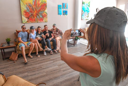 Kathleen Grace (right), owner of the new  Fort Pierce 212° Coffee House, photographs new customers (from left) Demetre Mendoza, Anna Bach, Christina Champagne, Tyler Kradzinski, and Al Hammock, as they pose while inside Grace's new coffee house at 127 North Second Street in Downtown Fort Pierce.