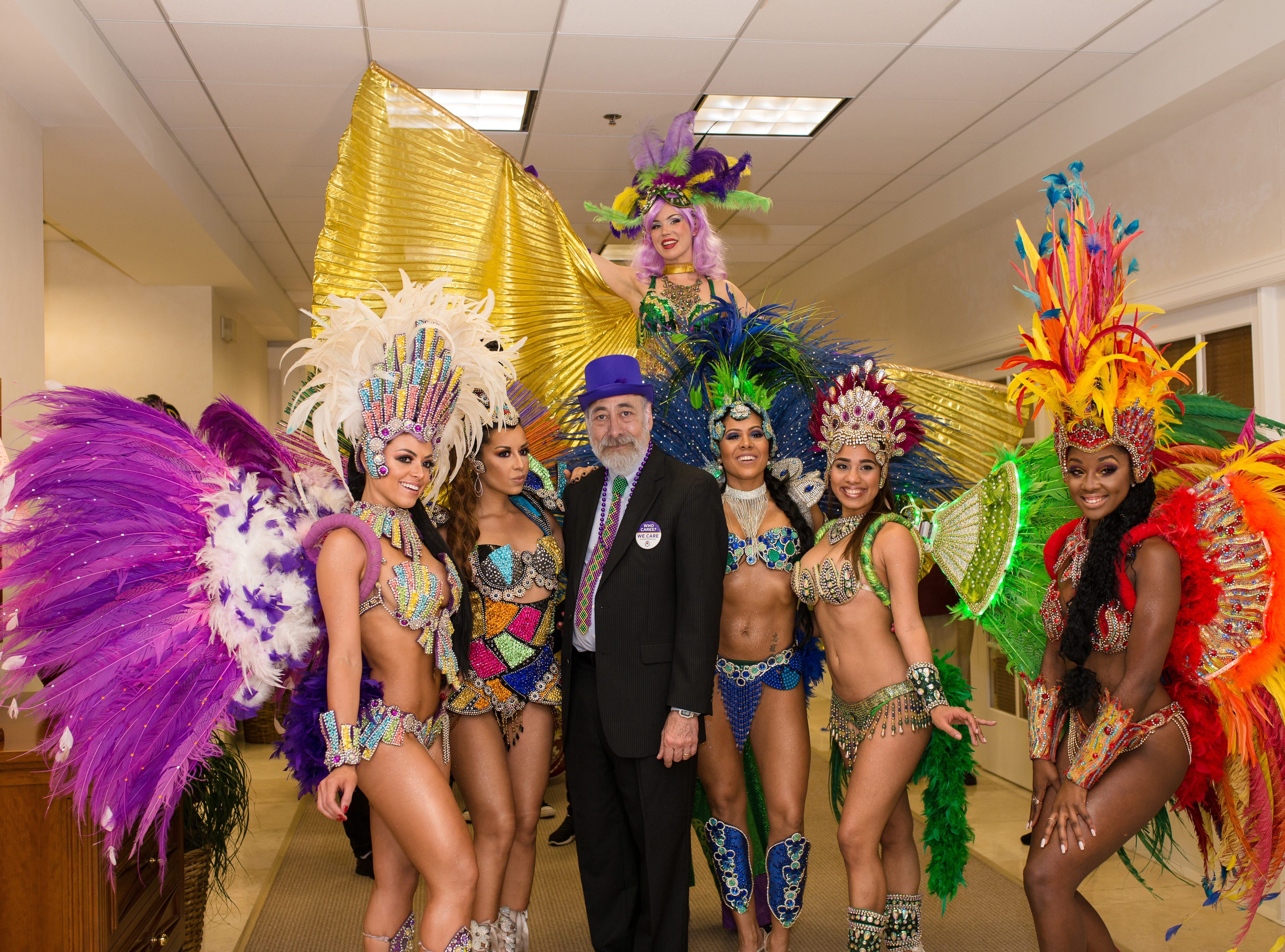 Dr. Dennis Saver, founder of the We Care Program, is surrounded by Phoebe's Samba Team prior to their performance at the Mardi Gras Celebration at Oak Harbor Club.