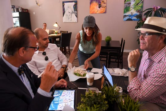 "New customers Joe Cronk (from left), Erlys Rodriguez, and Cliff Duch (right), from an architecture firm in Palm Beach, are served by Kathleen Grace (center), owner of the new  Fort Pierce 212° Coffee House, after they stopped in for breakfast on Monday, March 4, 2019, in downtown Fort Pierce. ""I think it's great,"" Cronk said about his breakfast experience. ""Great people, good attention to service, and a nice feel to it."""