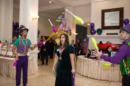 We Care Krewe member Hala Laviolette is center stage and keeping her fingers crossed as jugglers toss bowling pins over her head.