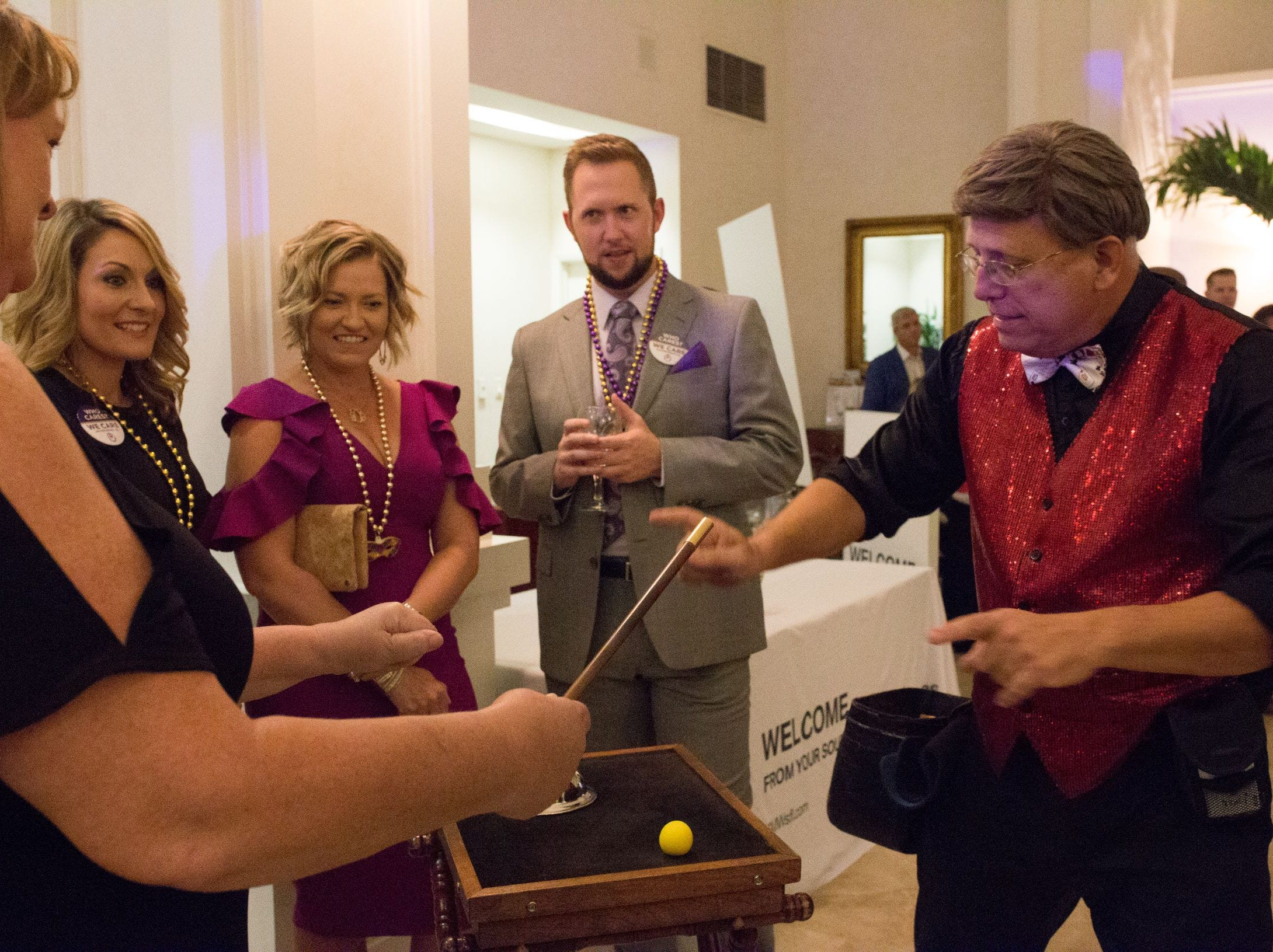 Magician David Kelly, right, entertains Mardi Gras guests Elizabeth White, left, Dyan Kurth and Ben Earman with sleight of hand tricks.