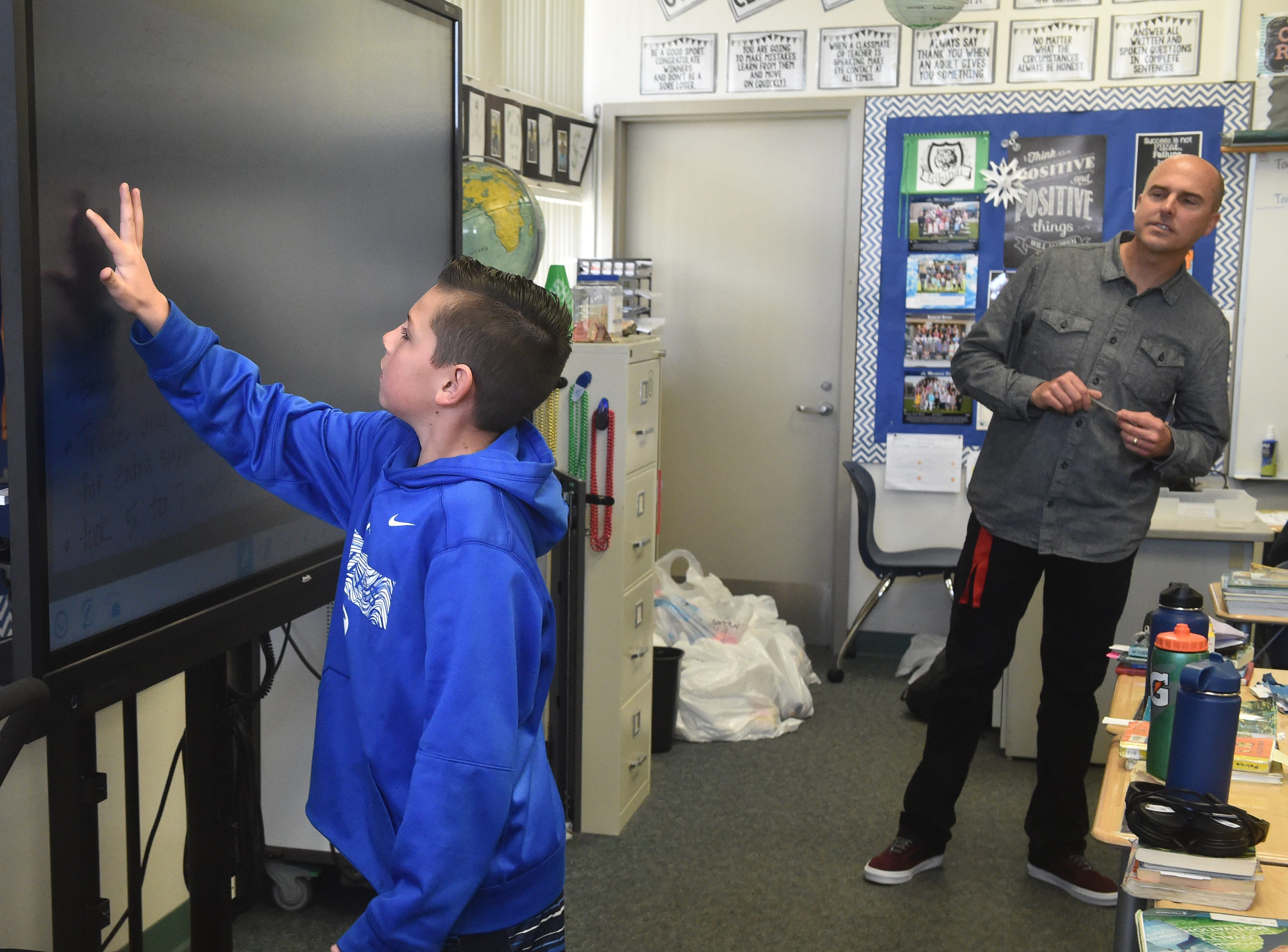 Cohen Tullis, a fourth-grader at Mariposa School in Camarillo, uses a new touch-screen display during class on a recent Monday as teacher Dave Ford looks on. The Pleasant Valley School District is using funds from Measure C to purchase technology for the classrooms.