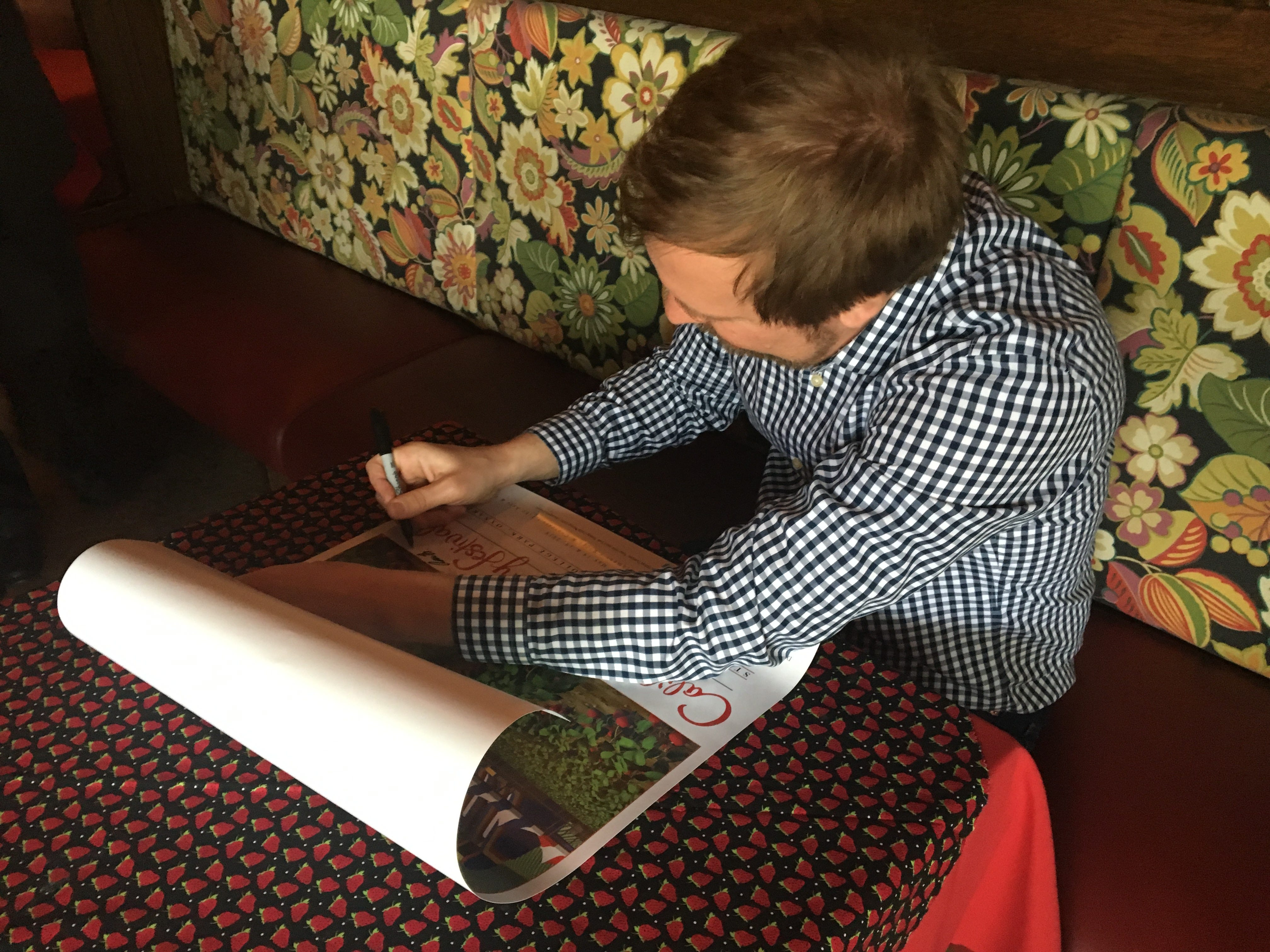 "Aaron Trask, of Glendale, signs copies of his work ""Monumental Strawberry,"" which has been selected as  the official poster of the 36th Annual California Strawberry Festival. The poster was unveiled at a ceremony Tuesday at Yolanda's Mexican Cafe in Oxnard."