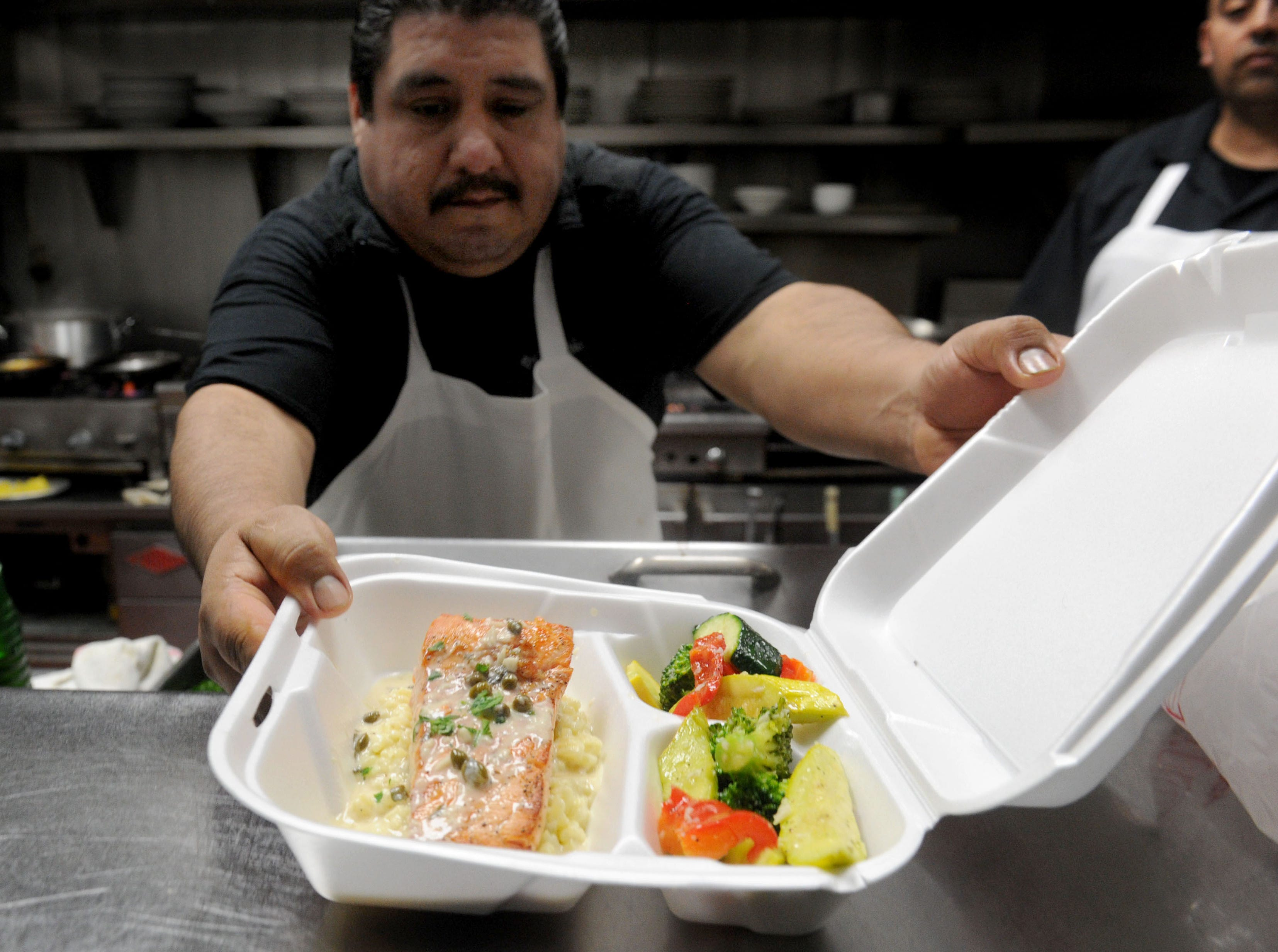 Augustine Resendiz, prepares a salmon dish to go at Bistro 13 in Camarillo.