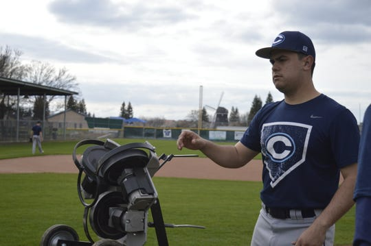 Central Valley Christian head baseball coach Shane Marshall loads the pitching machine at practice on March 4, 2019.