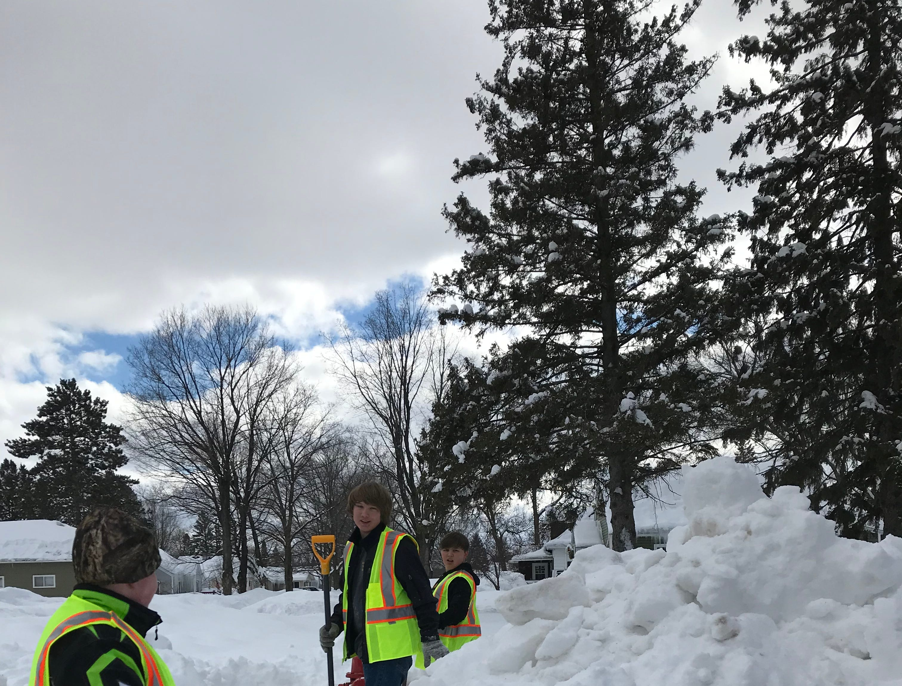 "Three of Merrill's ""hydrant heroes"" volunteer to dig out fire hydrants buried in snow."