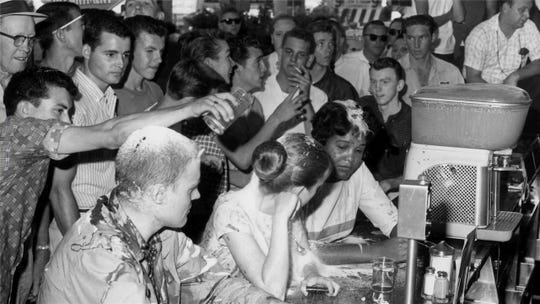 A mob opposed the demonstrators at a sit-in at Woolworth's lunch counter in Jacksonson, Miss., on May 28, 1963. A man is pouring sugar over the head of Joan Trumpauer Mulholland. Seated to her left is Anne Moody and to her right is John Salter Jr. Of the three, Mulholland is the only one still living.