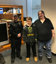 Officer Tyler Tesch with the Merrill Police Department, left, poses with 13-year-old Michael Dickman, middle, and Lonnie Scott, right. Dickman was formally recognized by the police department after he rescued Scott, who was stranded in the snow, from potential hypothermia at the end of February.