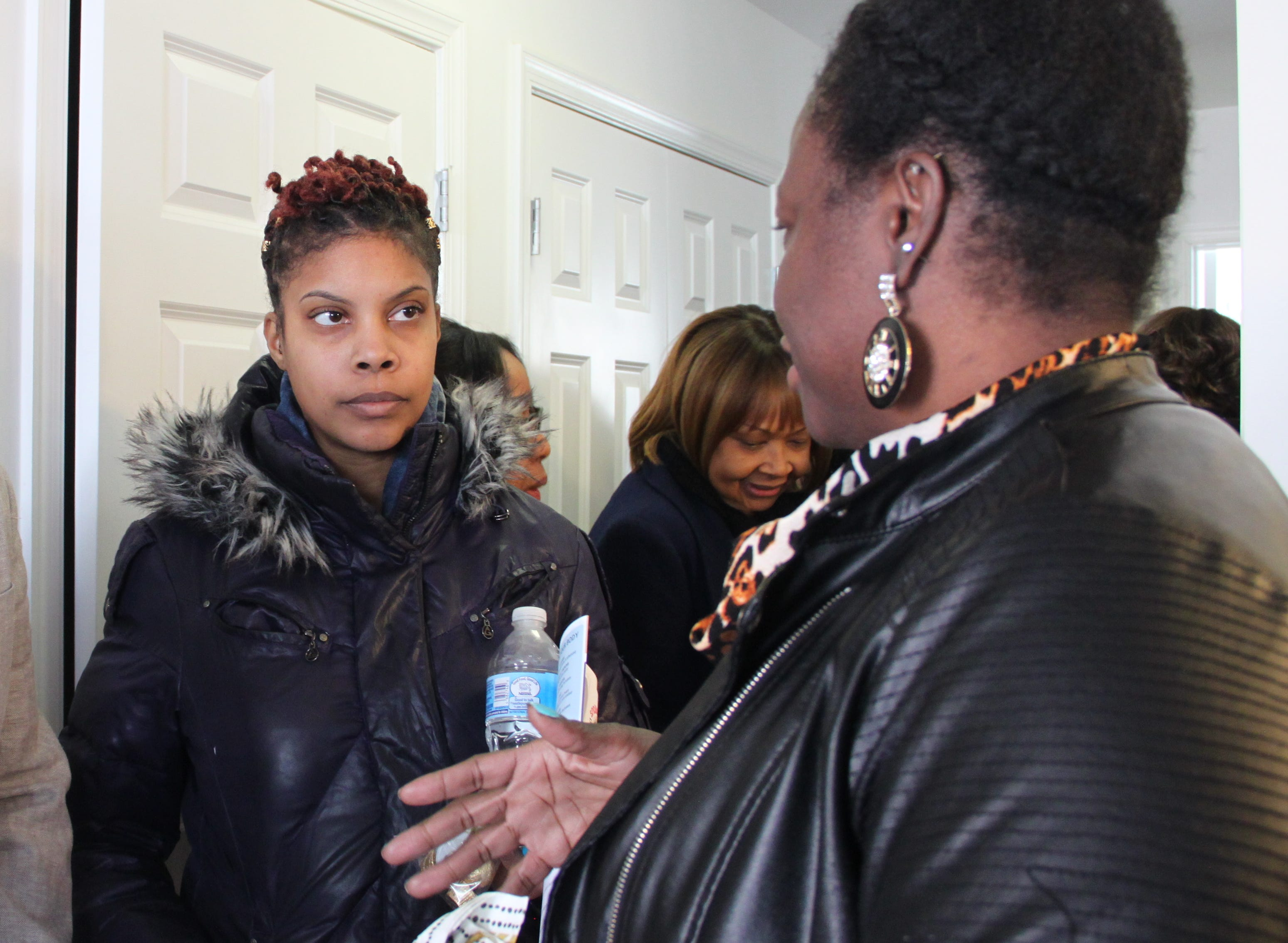 Jalisa White, left, listens to a fellow Riverside public housing resident during a tour of an Annapolis housing development. Similar housing plans could be used in a comprehensive revitalization of the Riverside neighborhood.