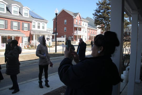 Sonia Paredes, right, a Riverside resident, takes pictures of an Annapolis housing development, a glimpse of what the Riverside public housing project could look like in the future